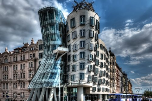I have about 500 shots of the Dancing House in Prague from every possible angle, portrait and landscape. They've been sitting on my disk for almost 2 years. I didn't know how to process them as the light was not great and an early attempt using Photomatix was a disaster.ISO 100, 14mm, f6.3, (1/1600, 1/400, 1/100 secs).I chose the f-stop so that I would get fast enough speed for the moving cars. Blended and tonmeppaed in Photomatix using Details Enhancer. Reduced noise in Imagenomics Noiseware. Carefully straightened the vertilcals using the Lens Correction filter in PS as the whole point if the building is it's vertical lines. Used the Freaky Details technique to get lots of details on the windows, etc. Used Nik Viveza to reduce the white glow around the building that was left over from Photomatix processing (masking the clouds). Used 15% Nik Glamour Glow to reduce the harshness of the Photomatix and Freaky Details.